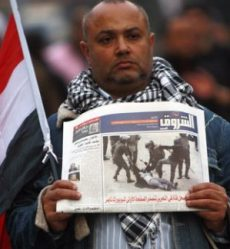 Protester in Egypt with an newspaper from Tahir Square